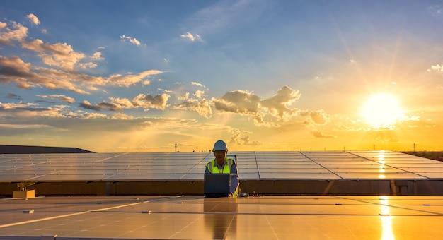 Inżynier używający laptopa przy panelach słonecznych na dachu o zachodzie słońca niebo inżynier pracujący przy fotowoltaice
