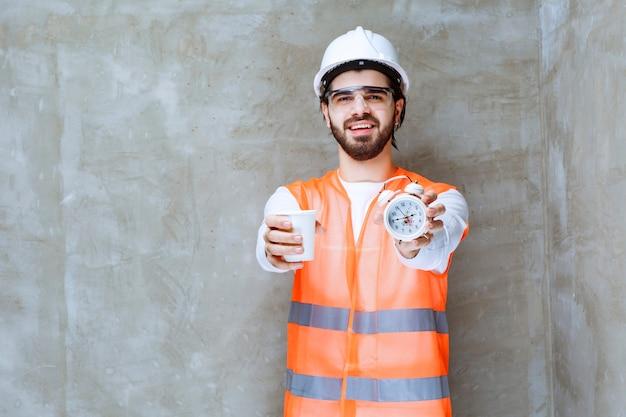 Inżynier w białym kasku i okularach ochronnych oferujący partnerowi budzik i filiżankę napoju.