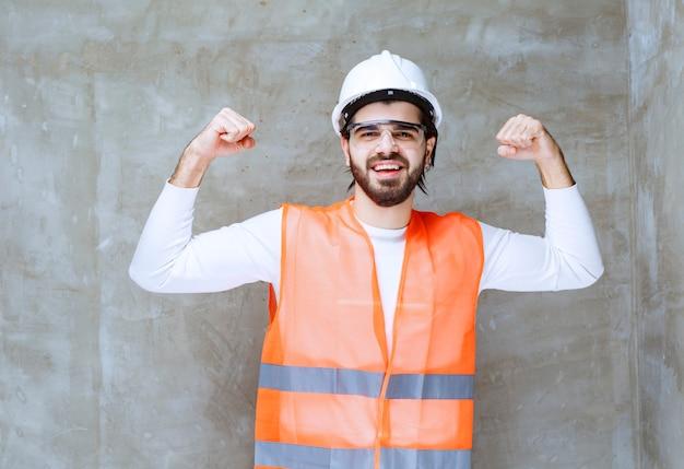Inżynier w białym kasku i okularach ochronnych pokazujących mięśnie ramion.