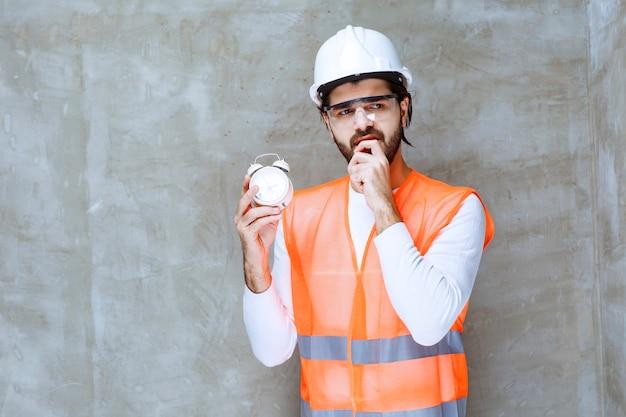 Inżynier w białym kasku i okularach ochronnych trzymający budzik i wyglądający na zdezorientowanego i zagubionego.