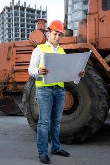 Inżynier w kasku czyta instrukcję do spychacza na placu budowy