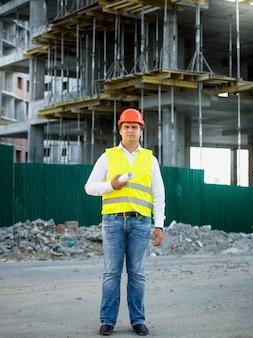 Inżynier w kasku na placu budowy pozujący przed rusztowaniem