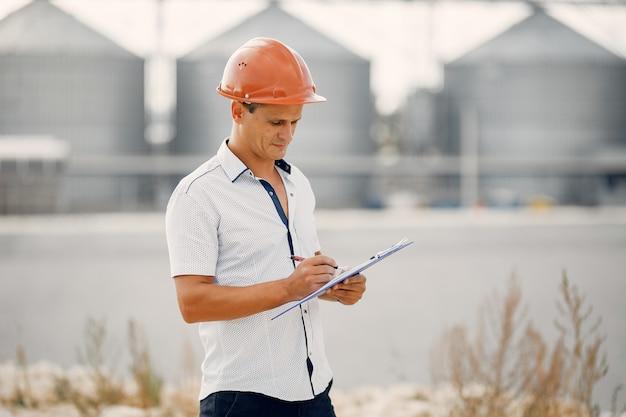Inżynier w kasku stojący przy fabryce