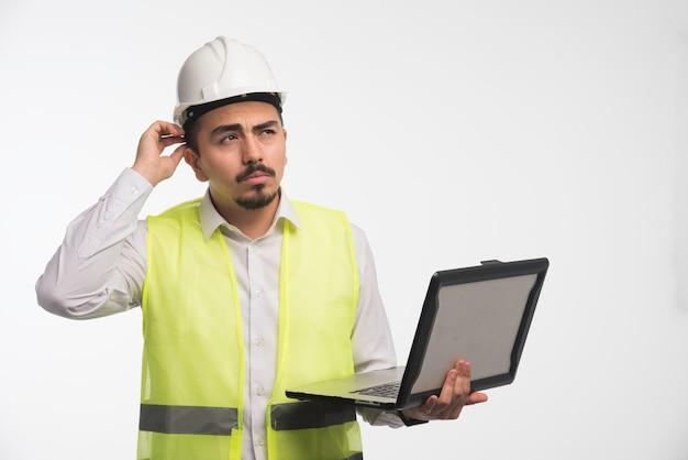 Inżynier w mundurze trzyma laptopa i myśli.