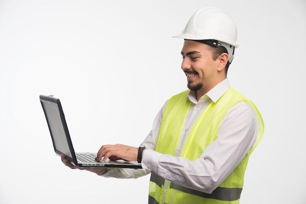 Inżynier w mundurze trzyma laptopa i pisze.