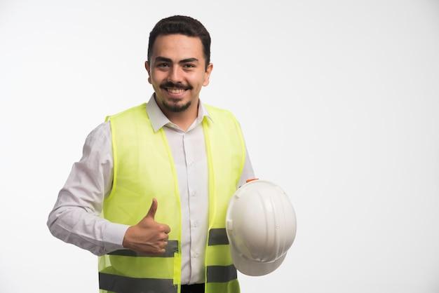 Inżynier w mundurze trzymający biały hełm.