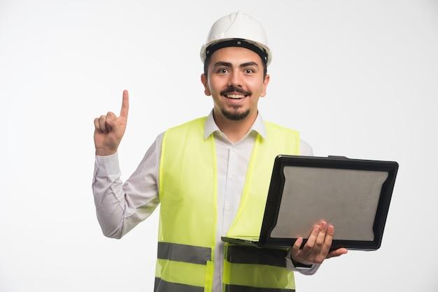 Inżynier w mundurze trzymający laptopa i mający pomysł.
