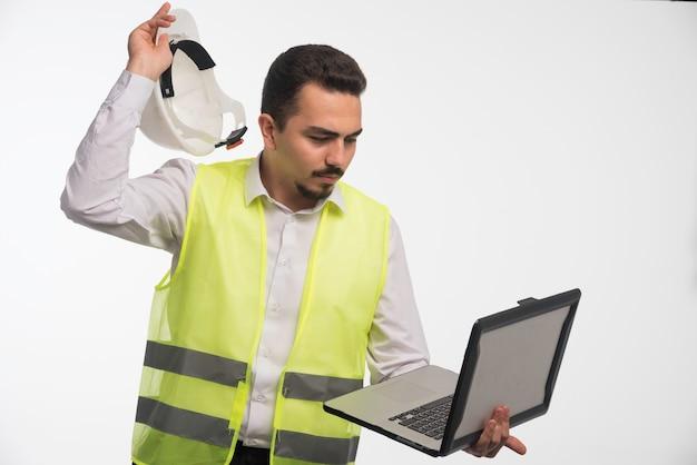 Inżynier w mundurze trzymający laptopa i wyjmujący hełm.