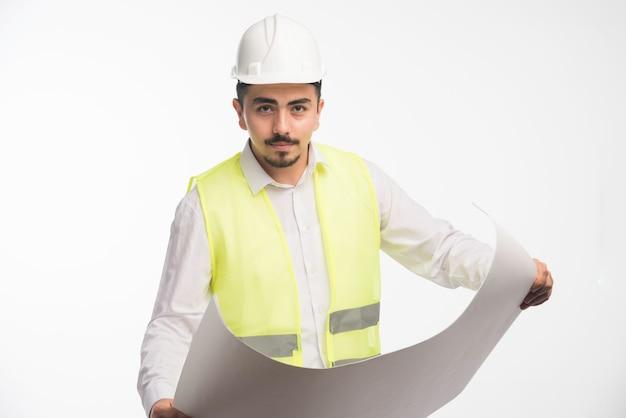 Inżynier w mundurze trzymającym plan architektoniczny budowy.