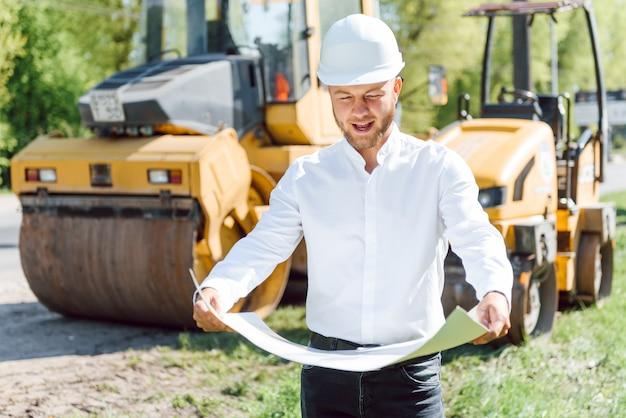 Inżynier w pobliżu maszyn drogowych. koncepcja budowy nowej drogi asfaltowej. naprawa dróg. pracownik służby drogowej w pobliżu lodowiska.