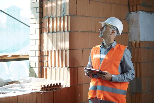Inżynier w pomarańczowej kamizelce i białym hełmie kontrolnym przeprowadza inspekcję z tabletem w rękach.