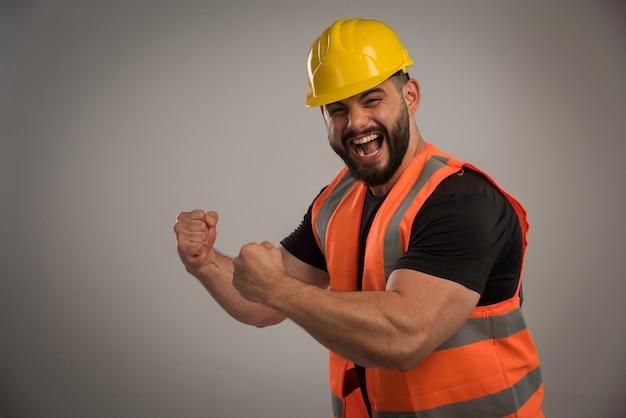 Inżynier w pomarańczowym mundurze i żółtym hełmie z dużymi mięśniami.