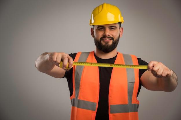 Inżynier w pomarańczowym mundurze i żółtym hełmie za pomocą linijki