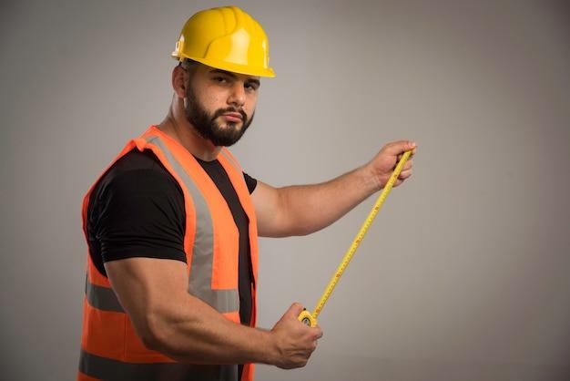 Inżynier w pomarańczowym mundurze i żółtym hełmie za pomocą linijki.