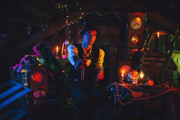 Inżynier w steampunkowym garniturze, cylindrze z laską w ręku siedzi w warsztacie zegarmistrzowskim przy świetle neonu. cyberpunkowy cosplay