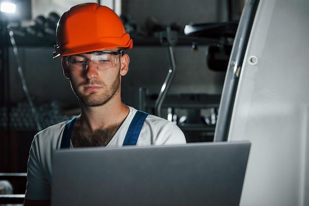 Inżynier w swoim miejscu pracy z laptopem. mężczyzna w mundurze pracuje nad produkcją. nowoczesna technologia przemysłowa.