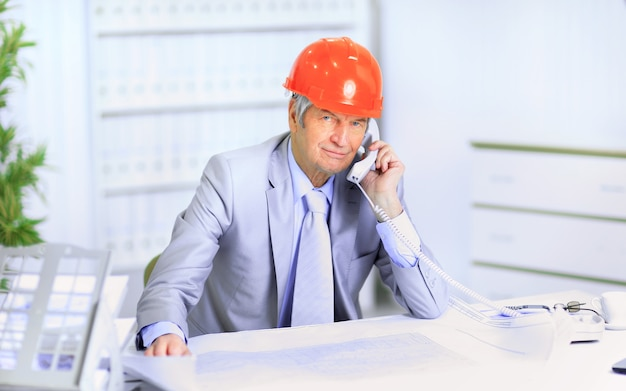 Inżynier w wieku rozmawiającego przez telefon o planach rysunku.