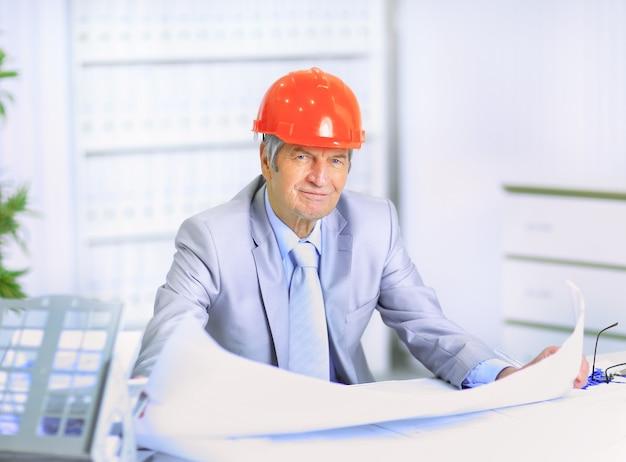Inżynier w wieku rozważania rysowania planów i ich poprawiania.