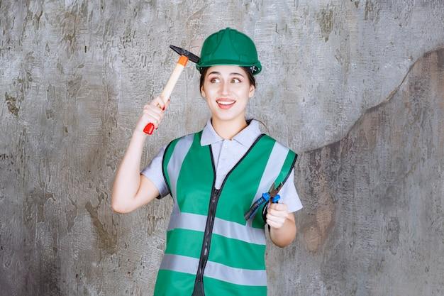 Inżynier w zielonym hełmie, trzymający szczypce i siekierę z drewnianą rękojeścią do naprawy