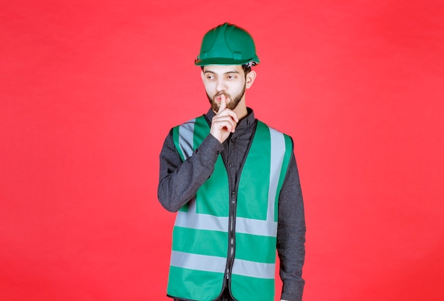 Inżynier w zielonym mundurze i hełmie proszący o ciszę.