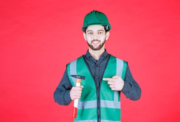 Inżynier w zielonym mundurze i hełmie, trzymający drewnianą siekierę.