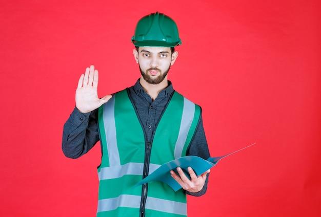 Inżynier w zielonym mundurze i hełmie trzymający niebieską teczkę, czytający i dokonujący poprawek.