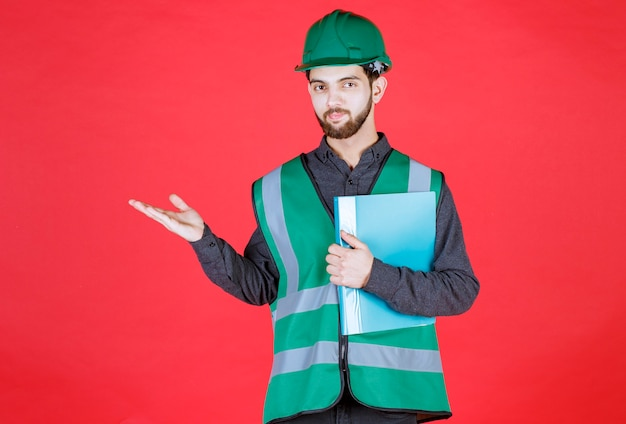 Inżynier w zielonym mundurze i hełmie trzymający niebieską teczkę i wskazujący coś po lewej stronie.