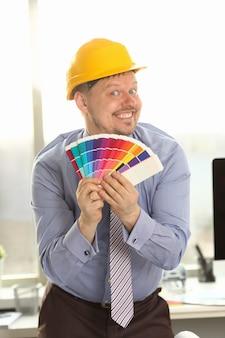 Inżynier w żółtym hełmie przedstawiający próbki kolorów
