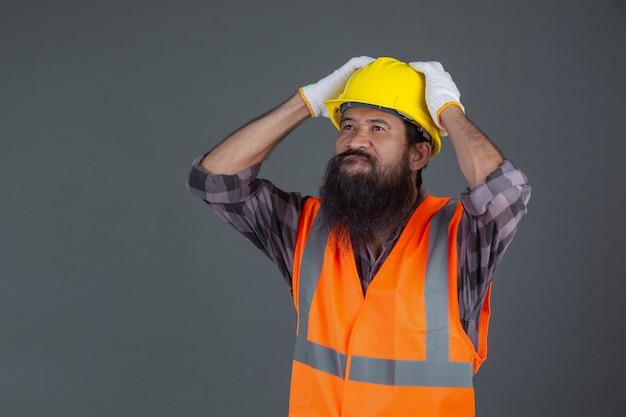 Inżynier w żółtym hełmie w białych rękawiczkach pokazał gest na szaro.