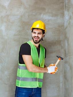 Inżynier w żółtym kasku i przemysłowych rękawicach uderza siekierą w betonową ścianę