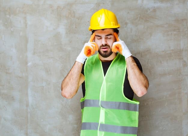 Inżynier w żółtym kasku i przemysłowych rękawiczkach czuje się zmęczony i śpiący