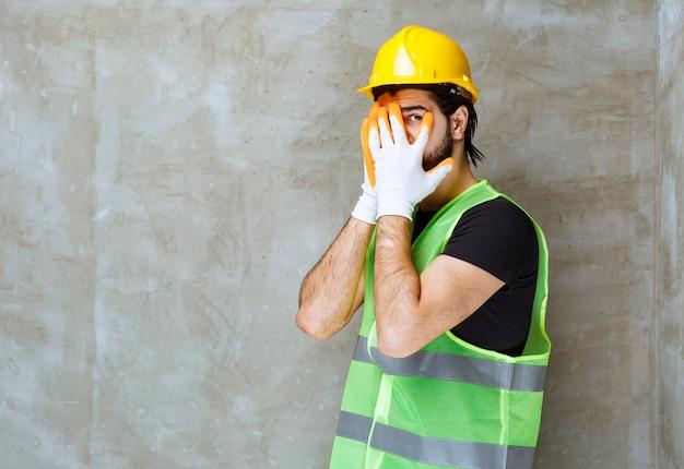 Inżynier w żółtym kasku i przemysłowych rękawiczkach patrzący przez palce