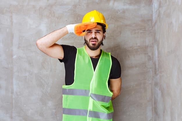 Inżynier w żółtym kasku i przemysłowych rękawiczkach przykłada rękę do czoła i obserwuje