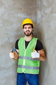 Inżynier w żółtym kasku i przemysłowych rękawiczkach, trzymający niebieskie szczypce i pokazujący kciuk w górę