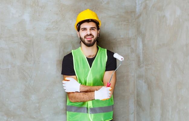 Inżynier w żółtym kasku i przemysłowych rękawiczkach trzymający wałek do malowania