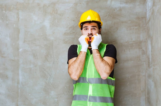 Inżynier w żółtym kasku i przemysłowych rękawiczkach wygląda na przestraszonego i przerażonego