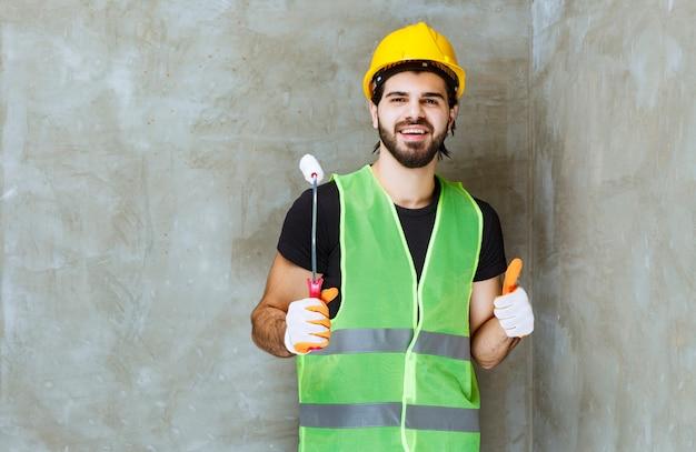 Inżynier w żółtym kasku i rękawicach przemysłowych trzymający wałek do malowania i cieszący się produktem