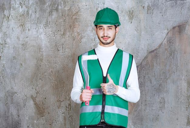 Inżynier w żółtym mundurze i kasku, trzymający rolkę do malowania ścian i pokazujący pozytywny znak ręki.