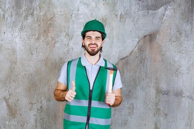 Inżynier w żółtym sprzęcie i hełmie, trzymający drewnianą siekierę z rękojeścią i pokazując kciuk do góry.