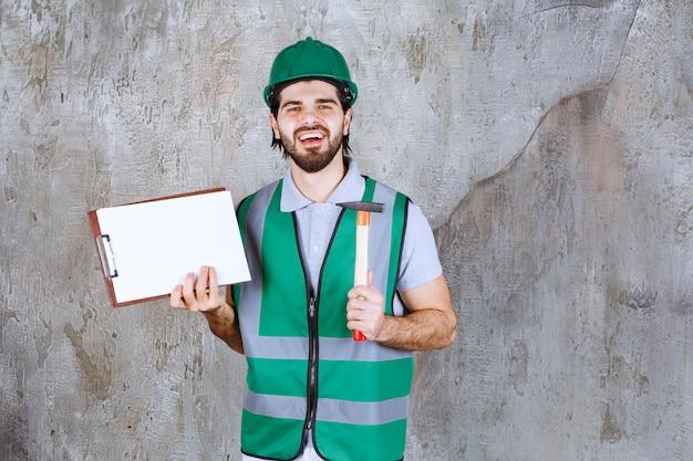 Inżynier w żółtym sprzęcie i hełmie, trzymający siekierę z drewnianą rękojeścią i listę zadań