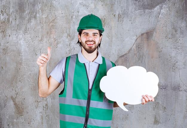 Inżynier w żółtym sprzęcie i kasku trzymający tablicę informacyjną w kształcie chmury i cieszący się tym projektem