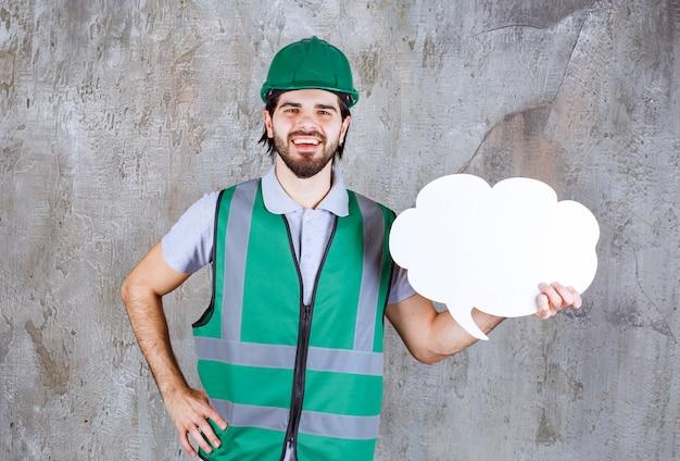 Inżynier w żółtym sprzęcie i kasku trzymający tablicę informacyjną w kształcie chmury.