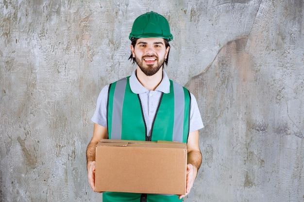 Inżynier w żółtym stroju i hełmie, trzymający kartonowe pudełko.