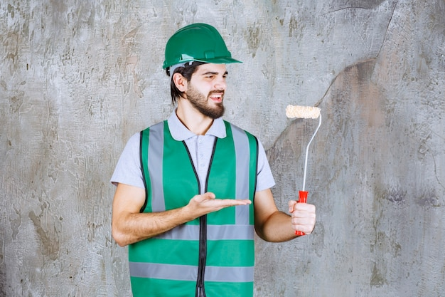 Inżynier w żółtym stroju i kasku trzymający rolkę do przycinania.