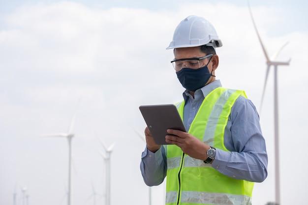 Inżynier wiatraków w masce na twarz i na tablecie z turbiną wiatrową w tle