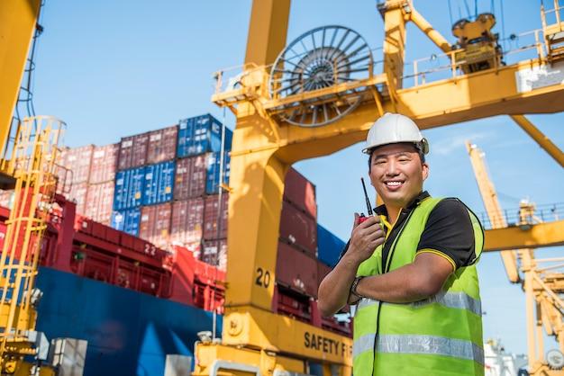 Inżynier współpracujący z kontenerowym statkiem towarowym w stoczni dla logistic import export