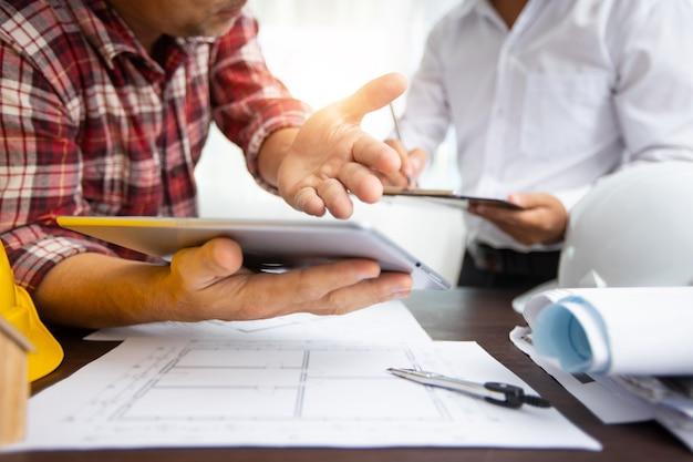 Inżynier wyjaśniający prace projektowe na tablecie