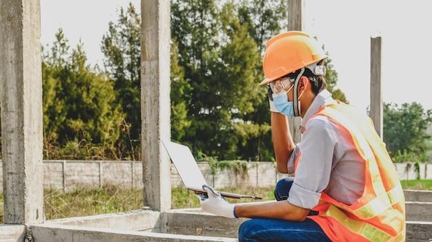 Inżynier wykonawca człowiek używa laptopa projekt branży bezpieczeństwa pracy sprawdź projekt planu domu