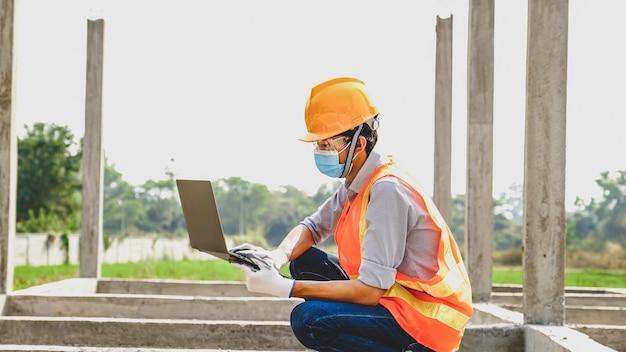 Inżynier wykonawca użyj laptopa praca projekt przemysłowy sprawdź projekt planu domu na placu budowy