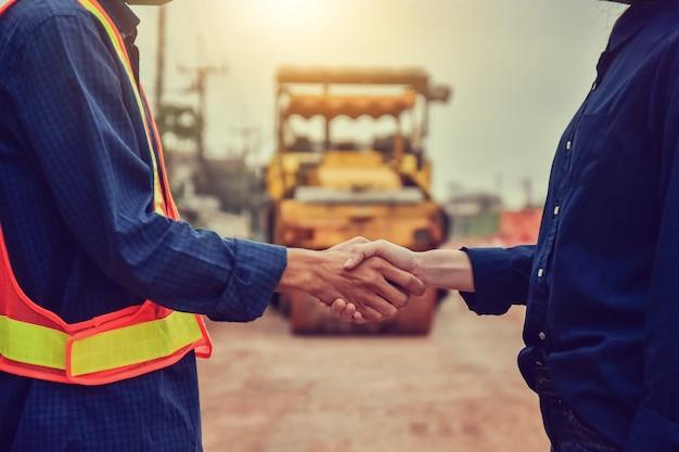 Inżynier z bliska uścisnąć dłoń na budowie
